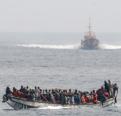 "Bootsflüchtlinge mit einem sich nähernden spanischen Seenotrettungsschiff. In überfüllten Flüchtlingsbooten versuchen tausende Menschen nach Europa zu kommen. Viele von ihnen sterben auf hoher See. (Bild: ""Cayuco approached by a spanish Salvamar vessel"" von Noborder Network - Flickr: cayuco approached by a spanish coast guard vessel. Lizenziert unter CC BY 2.0 über Wikimedia Commons - http://commons.wikimedia.org/wiki/File:Cayuco_approached_by_a_spanish_Salvamar_vessel.jpg#/media/File:Cayuco_approached_by_a_spanish_Salvamar_vessel.jpg"