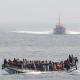 """Bootsflüchtlinge mit einem sich nähernden spanischen Seenotrettungsschiff. In überfüllten Flüchtlingsbooten versuchen tausende Menschen nach Europa zu kommen. Viele von ihnen sterben auf hoher See. (Bild: """"Cayuco approached by a spanish Salvamar vessel"""" von Noborder Network - Flickr: cayuco approached by a spanish coast guard vessel. Lizenziert unter CC BY 2.0 über Wikimedia Commons - http://commons.wikimedia.org/wiki/File:Cayuco_approached_by_a_spanish_Salvamar_vessel.jpg#/media/File:Cayuco_approached_by_a_spanish_Salvamar_vessel.jpg"""